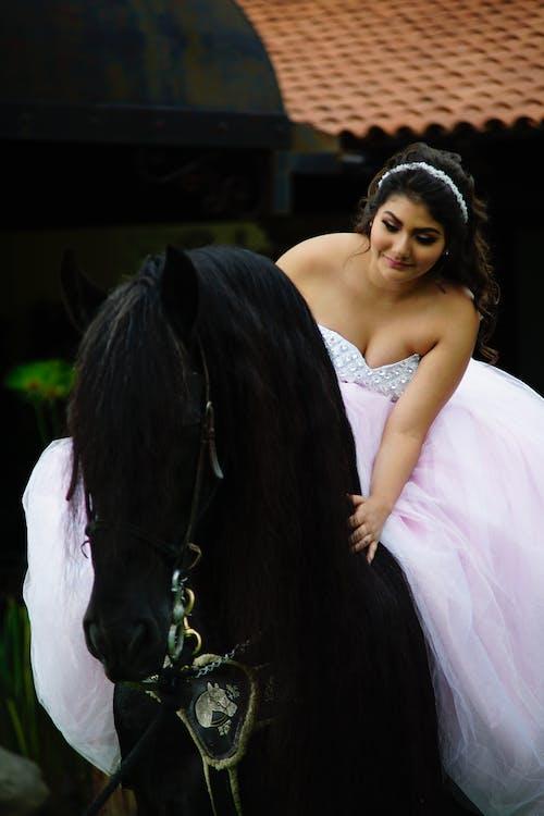 Woman in White Dress Beside Black Horse