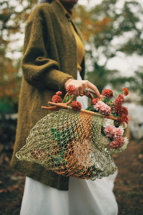 Crop woman in warm outfit carrying knitted shopper with red flowers
