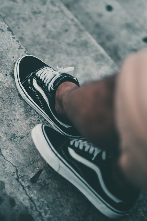 Person Wearing Pair of Black Vans Old Skool Low-tops