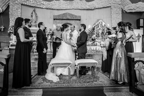 Bride and Groom Sitting on Chair in Grayscale Photography