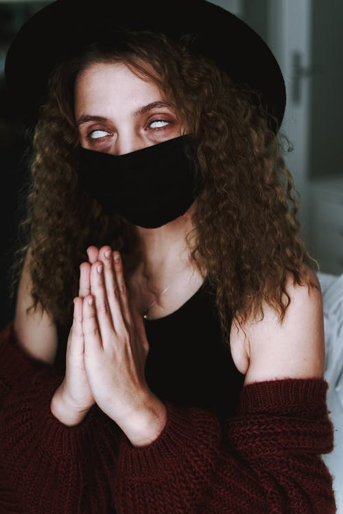 Woman in Black Tank Top Covering Face With Her Hand
