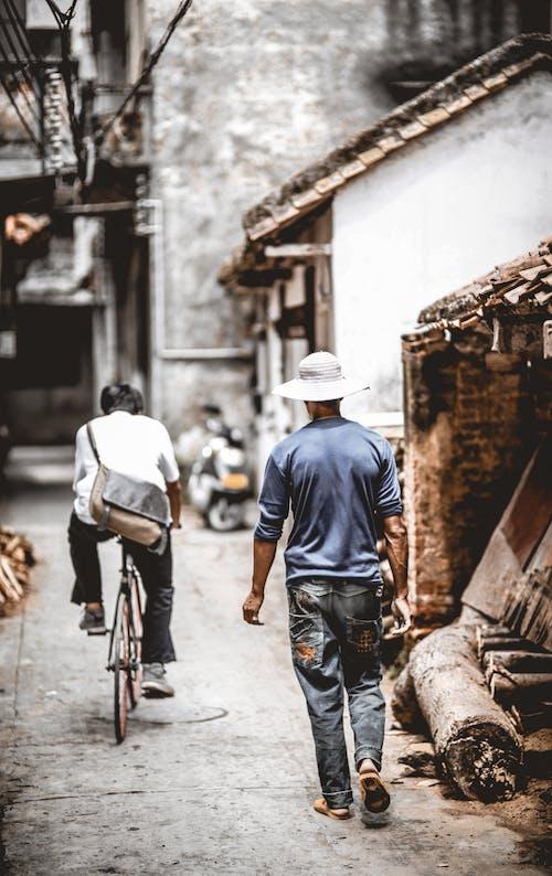 Faceless men walking and riding bicycle along dirty street