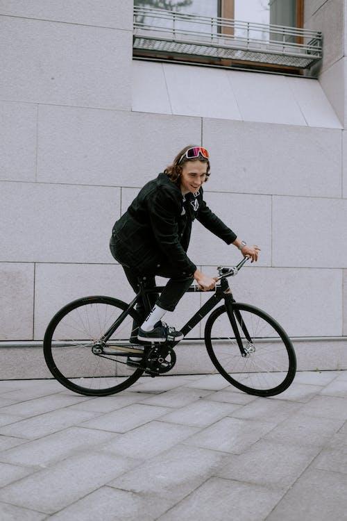 Man in Green Jacket Riding Black Bicycle