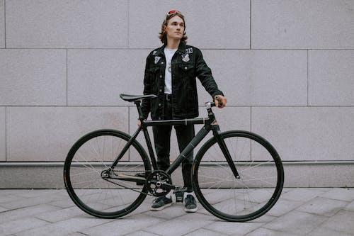 Woman in Black Jacket and Black Pants Standing Beside Black Bicycle