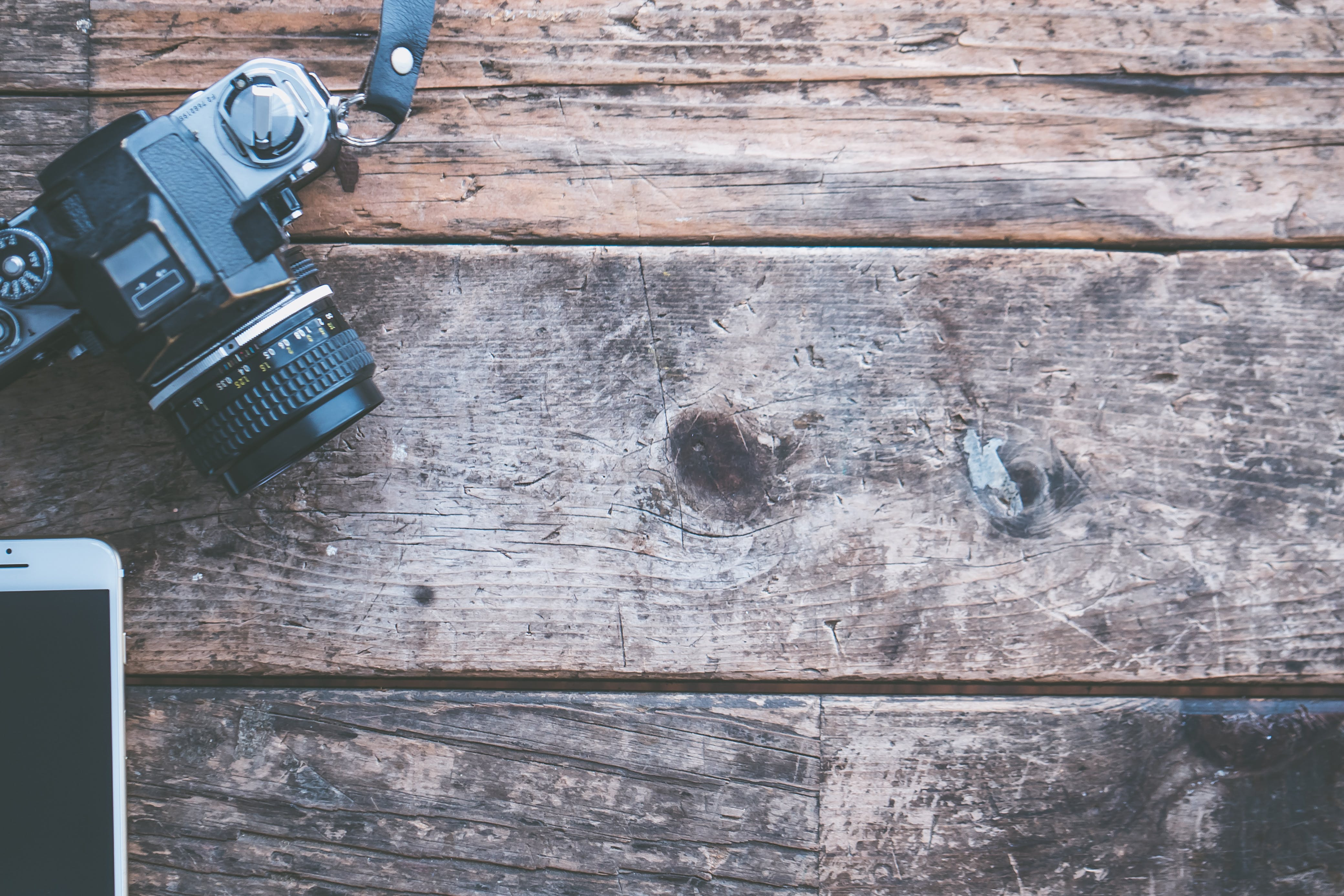 Black and Gray Dslr Camera on Brown Wooden Plank