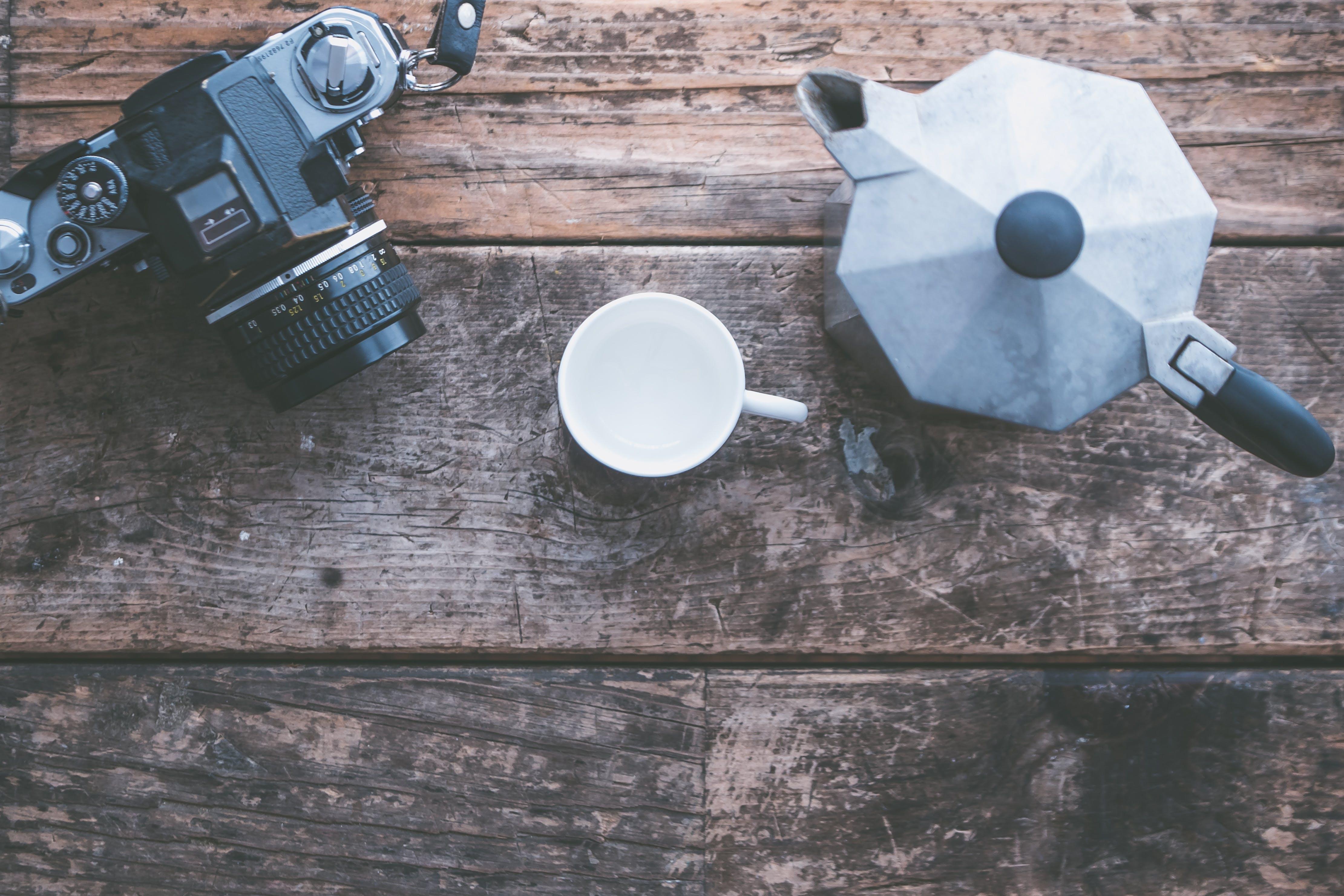 Black Slr Camera Beside White Ceramic Mug and Grey Teapot on Brown Wooden Table