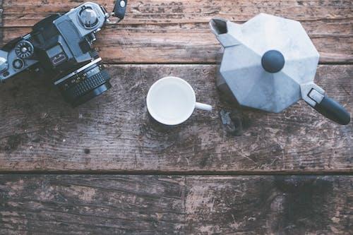 黑色单反相机旁边白色陶瓷杯和棕色木制的桌子上的灰色茶壶