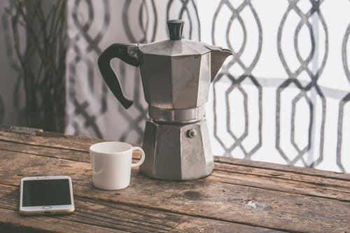 Gray Moka Pot Beside White Ceramic Cup on Brown Wooden Table