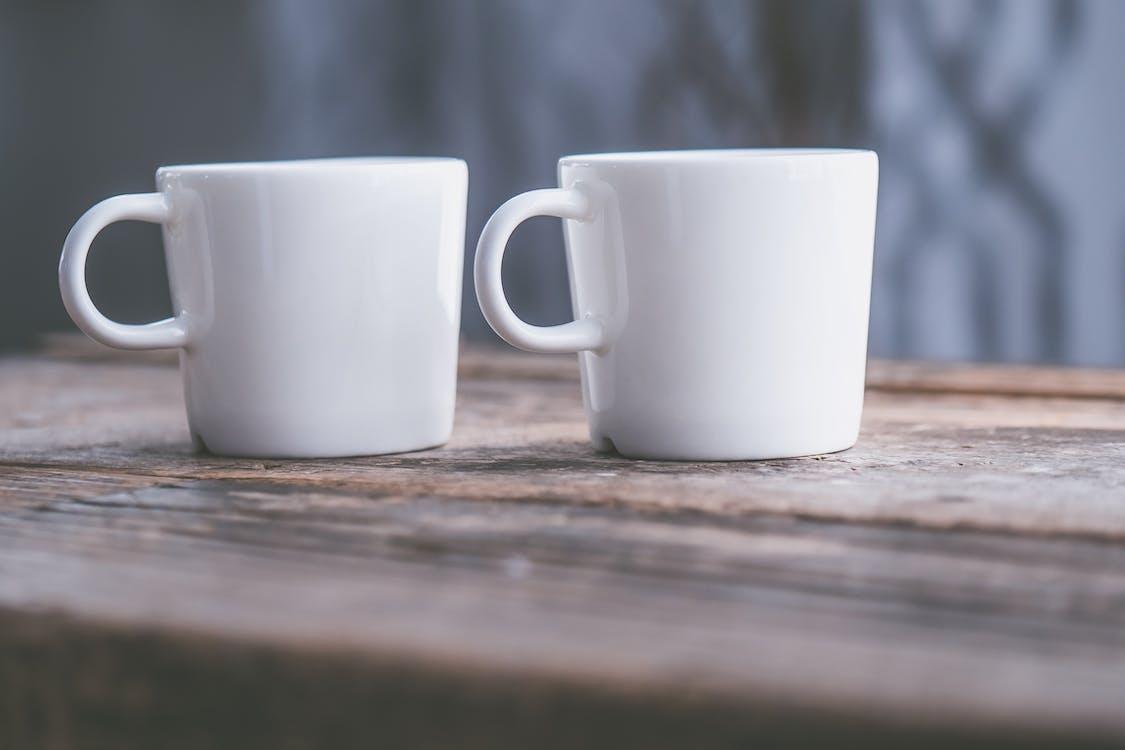 2つの白いセラミックマグカップ浅い焦点写真