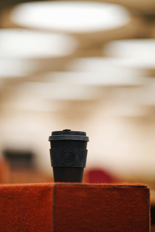 Black and Red Coffee Cup on Brown Wooden Table