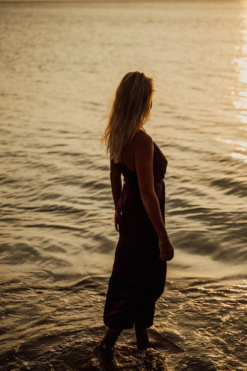Woman in Black Spaghetti Strap Dress Standing on Seashore