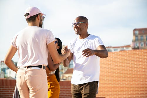 Happy smiling multiethnic male friends greeting each other and shaking hands while gathering on rooftop in urban city