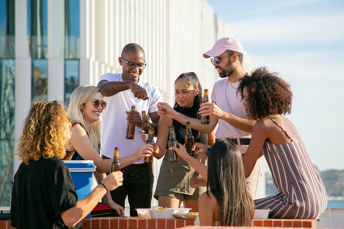 Group of cheerful multiracial friends in casual summer outfits toasting with beer bottles while having party on rooftop in urban environment