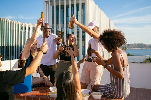 Joyful diverse friends toasting with beer bottles on rooftop