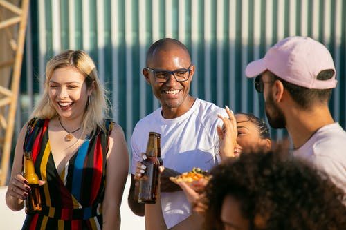 Laughing diverse friends with beer bottles having party on terrace