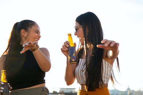 Attractive joyful female friends in summer wear enjoying cold beer and chatting happily while looking at each other with laughter