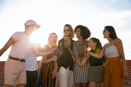 Group of joyful multiracial friends in summer outfits clinking beer bottles and laughing while gathering together on sunny rooftop