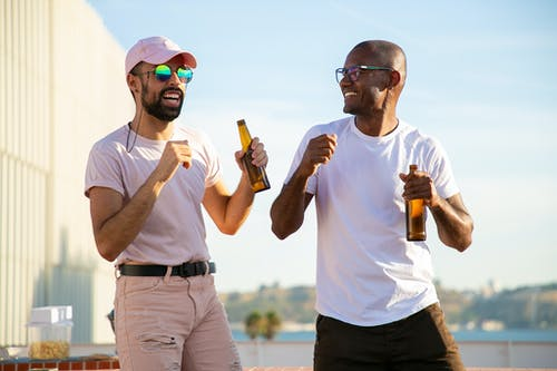 Happy multiracial male friends in summer clothes enjoying cold beer and dancing while attending party on sunny rooftop