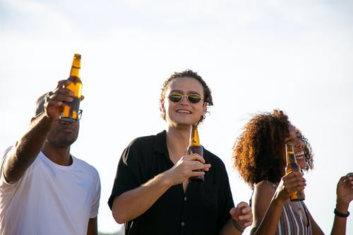 Cheerful diverse friends drinking beer during celebration party
