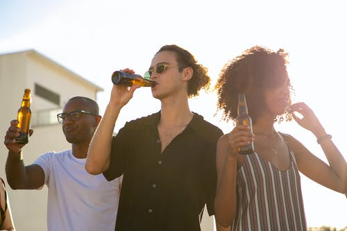 Diverse friends drinking bottles of beer during party outdoors