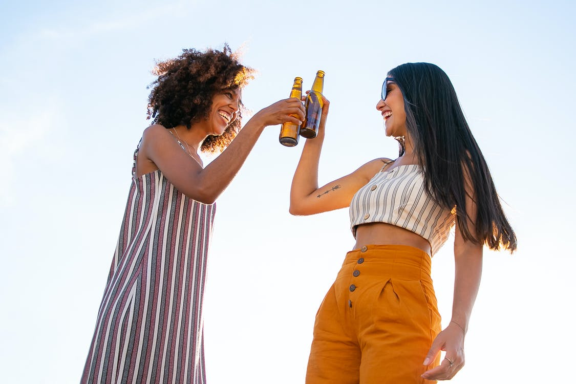 Low angle of delighted multiracial female friends toasting with bottles of beer while laughing together during party
