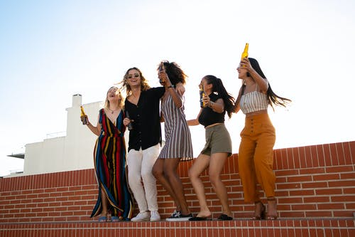 Low angle full body of multiracial friends having party with raised arms while celebrating together and drinking beer on rooftop