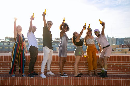 Happy multiethnic friends drinking beer and having fun during party on rooftop