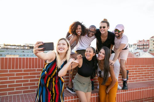 Group of cheerful young male and female multiracial friends laughing and taking selfie on smartphone while spending time together on terrace