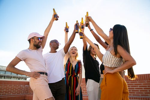 Group of cheerful multiethnic friends clinking beer bottles during event on terrace