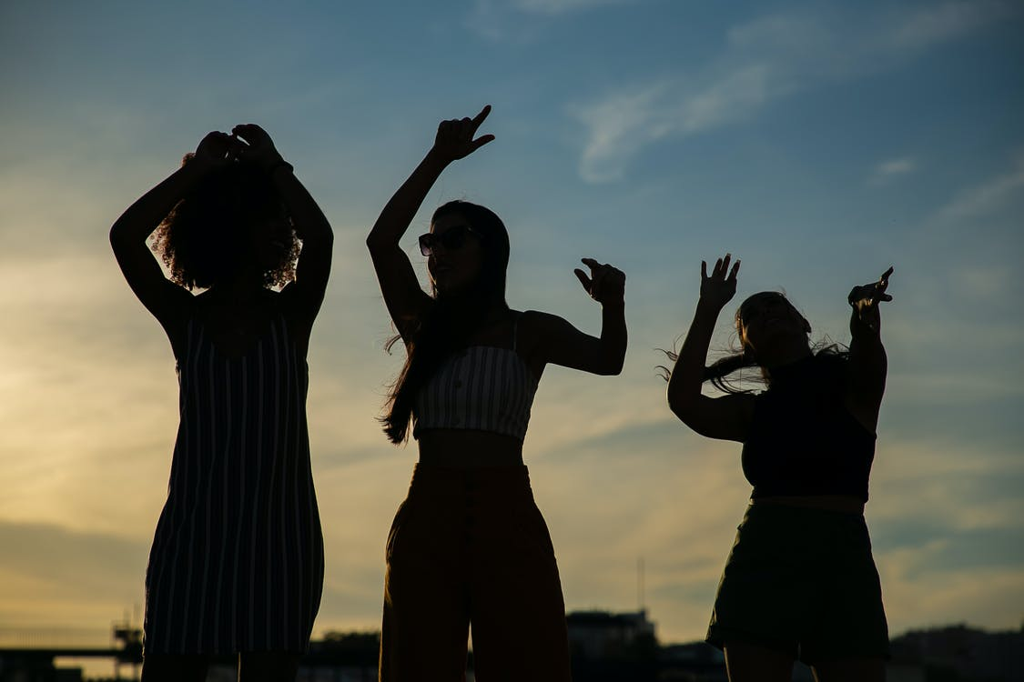 Low angle silhouettes of unrecognizable young female friends dancing against cloudy sunset sky during open air party