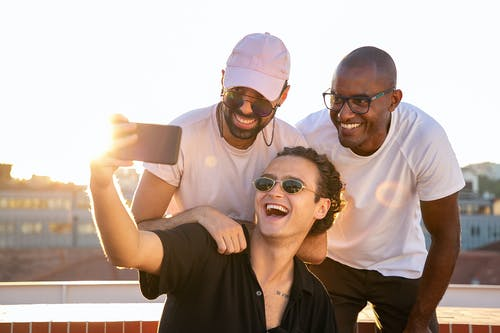 Cheerful young multiethnic men laughing and taking selfie on smartphone in sunlight