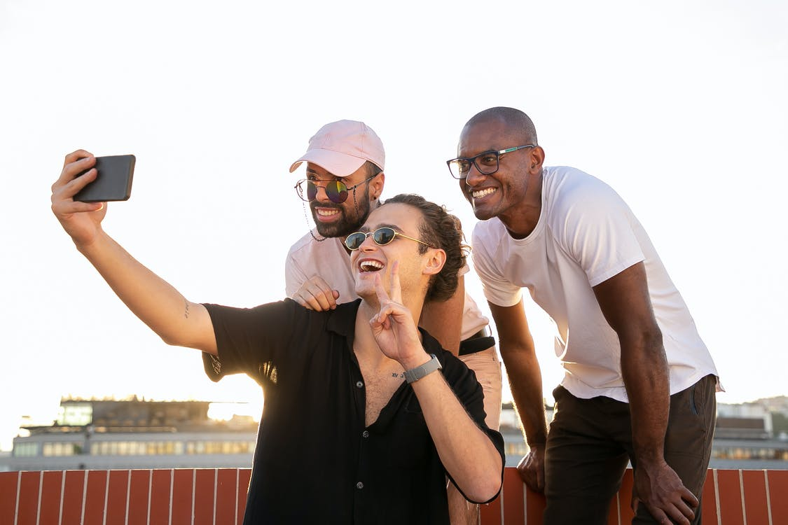 Low angle of positive young guy showing peace sign and smiling while taking selfie on smartphone with diverse friends on building rooftop