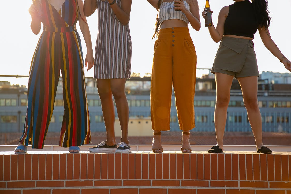 Faceless diverse women drinking beer during open air party on rooftop