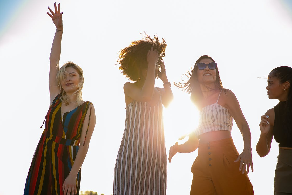 From below of young content diverse ladies in trendy outfits smiling and dancing against cloudless sky during open air party on sunny day