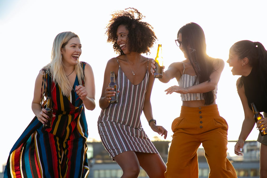 Group of cheerful young multiracial ladies laughing and dancing with beer bottles in hands during summer party on rooftop on sunny day
