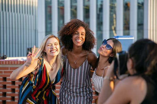 Unrecognizable female photographer taking picture of cheerful young multiracial female friends smiling and showing V sign during party on modern building rooftop
