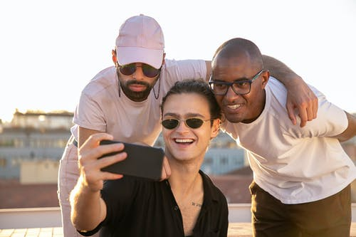 Content young multiethnic guys taking selfie on smartphone on rooftop