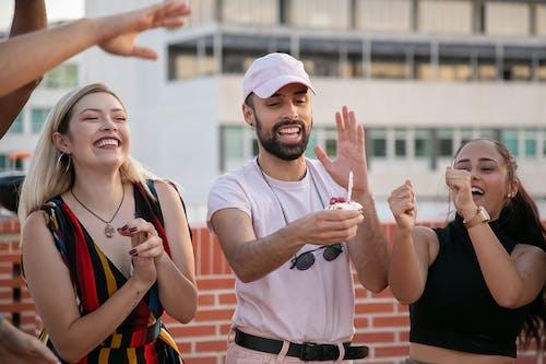 Gente Multirracial Positiva Bailando Mientras Celebra El Cumpleaños De Un Amigo étnico Con Cupcake En Mano