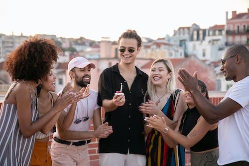 Joven Alegre Con Cupcake De Cumpleaños En La Mano Durante La Fiesta Con Amigos Diversos Felices