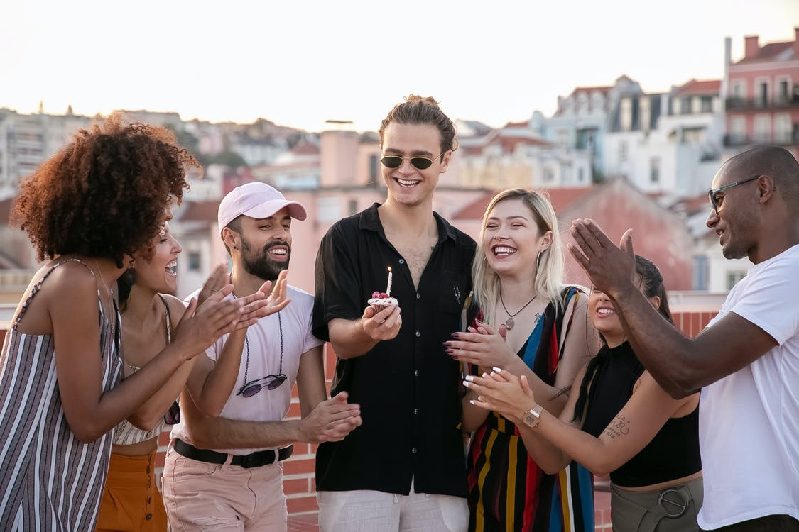 Group of positive young multiracial friends clapping and smiling while celebrating birthday of happy guy making wish with cupcake in hand on building rooftop