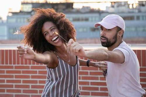 Joyful young African American female and ethnic guy having fun while dancing with sparklers in hands during open air party on modern building terrace