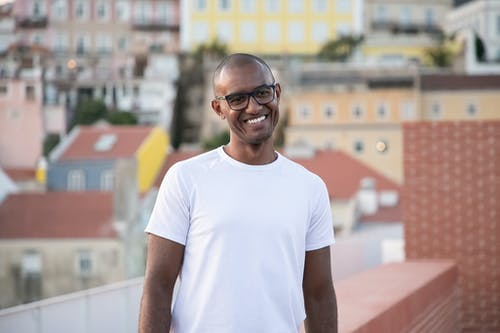 Positive young hairless African American male in white t shirt and eyeglasses smiling while standing on building rooftop on sunny day