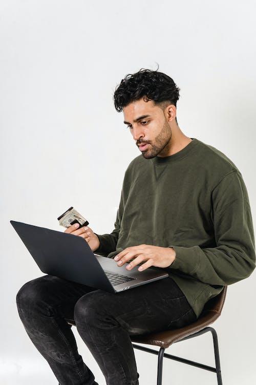 Homem Em Camisa Cinza De Manga Comprida Com Gola Redonda Usando Macbook