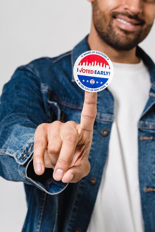 Man In Blue Denim Button Up Jacket Showing A Voting Sticker