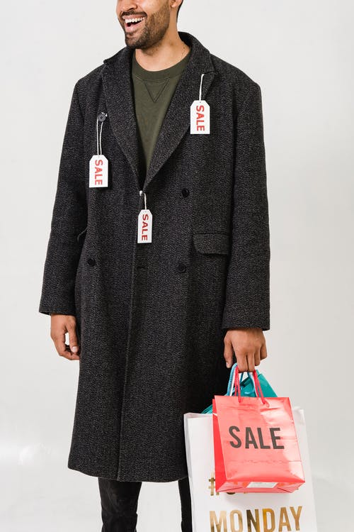 Man Wearing Gray Coat With Sale Tags