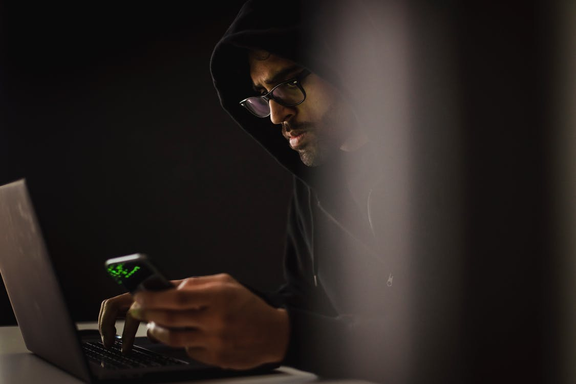 Crop ethnic hacker with smartphone typing on laptop in darkness