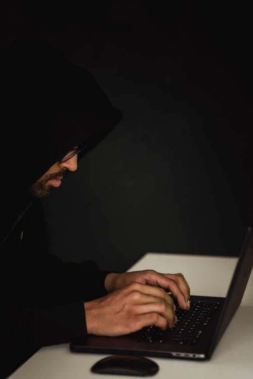 Side view of crop anonymous young ethnic male cyber spy in hoodie typing on portable computer on black background