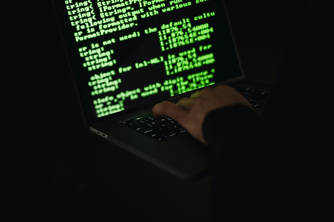 Crop hacker typing on laptop with information on screen