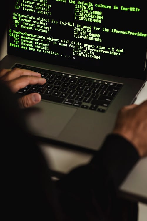 Crop anonymous male cyber spy hacking portable computer with codes on screen while sitting at table