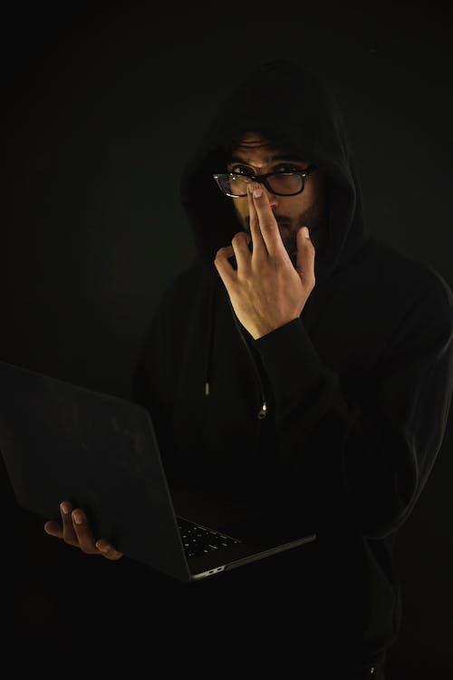 Geek Maschio Del Computer In Occhiali Con Il Computer Portatile Nelle Tenebre